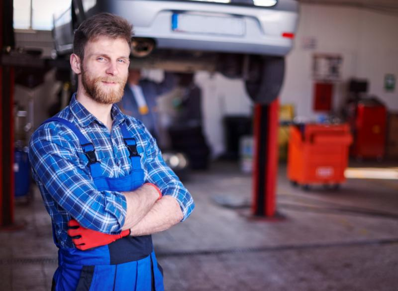 mechanic standing in shop in front of cars