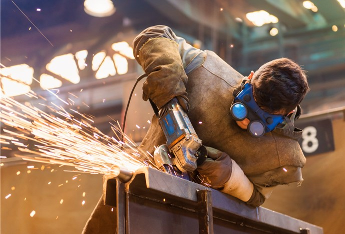 young man welding in factory